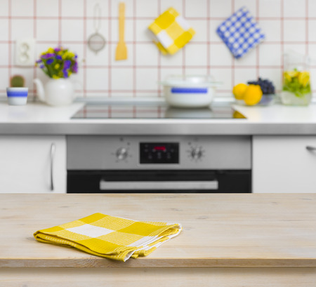 kitchen counter top: Wooden table with yellow napkin on kitchen background