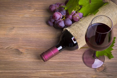vins: Bottle of wine, red grape and glass on wooden table Stock Photo