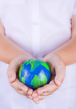 Child holding plasticine globe in hands photo