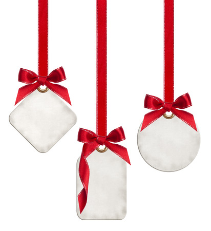 Collection of blank gift tags tied with red satin ribbon bows