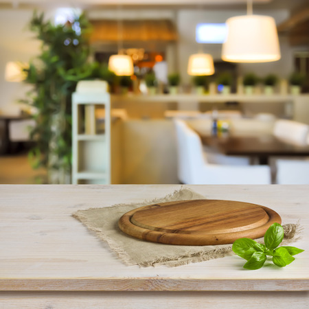 Cutting board on table over blurred restaurant interior background Foto de archivo