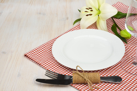 Served wooden restaurant table with settings on red checkered tablecloth