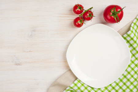 Food background with empty plate, tomatos and kitchen towel