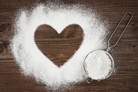 bolter: Heart shape of flour on brown wooden board background Stock Photo