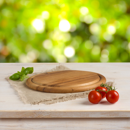 Kitchen table with round board over green bokeh background Stockfoto