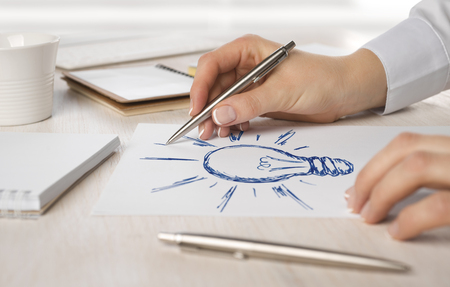 situation: Business woman hand drawing on paper a light bulb Stock Photo