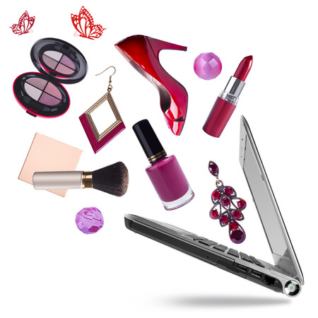 of cosmetics: Opening laptop pc with cosmetic products flying out on white