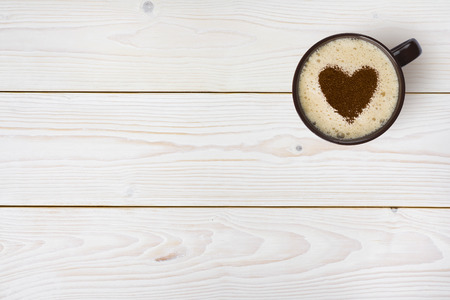 Top view of coffee cup with heart on wooden background Stock Photo