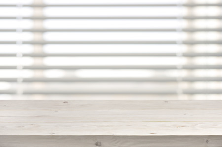 venetian blind: Wooden table from planks on window with venetian blinds background