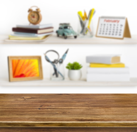 Wooden table on background of shelves with home related objects photo