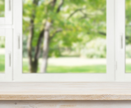 Wooden table over summer window background Imagens