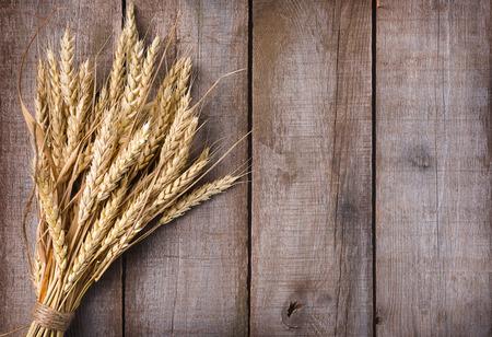 木製のテーブルに小麦の穂の束 写真素材