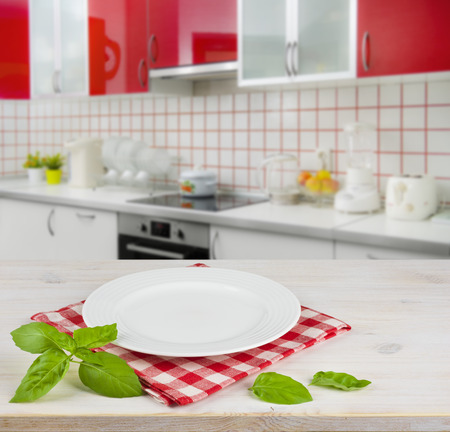 red kitchen: White plate on table placemat over modern kitchen interior background