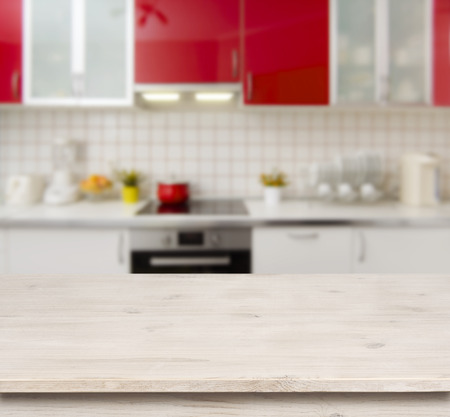 red kitchen: Wooden table on red modern kitchen bench interior background
