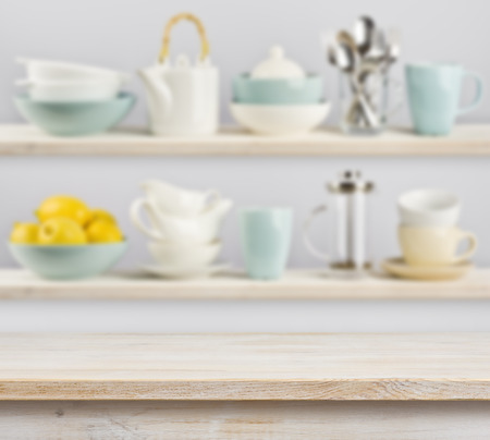Wooden table over background of shelves with kitchenware