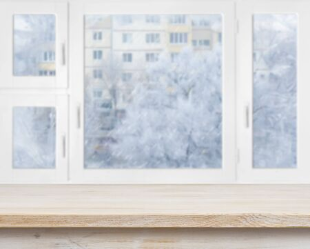 winter window: Wooden table surface over frosty window background Stock Photo