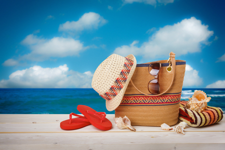 Bag, sunglasses, hat and flip flops on sea sky background