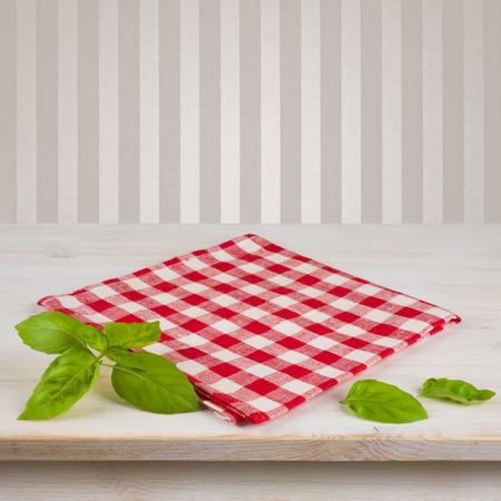 serviette: Red checkered napkin and leaves on table over vintage background Stock Photo