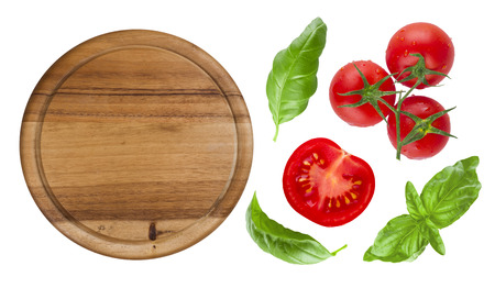 Top view of isolated cutting board with tomato and basil Archivio Fotografico