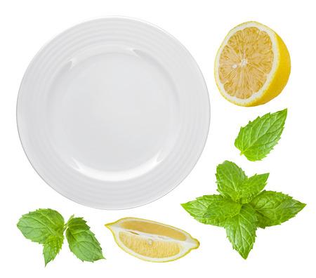plato de comida: Vista superior de un plato blanco aislado con lim�n y menta
