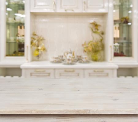 defocused 흰색 부엌 가구 배경에 표백 된 나무 테이블
