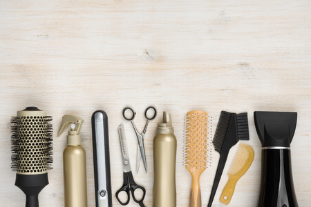 Hairdressing tools on wooden background with copy space at top Foto de archivo