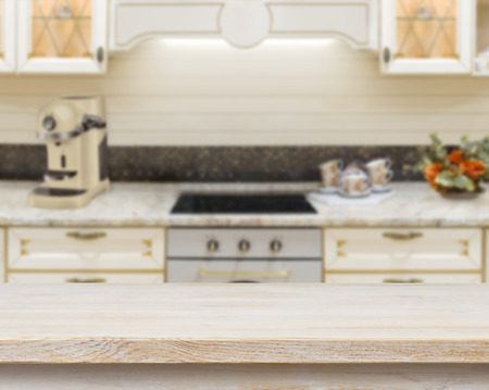 Wooden textured table over blurred kitchen stove interior background Standard-Bild