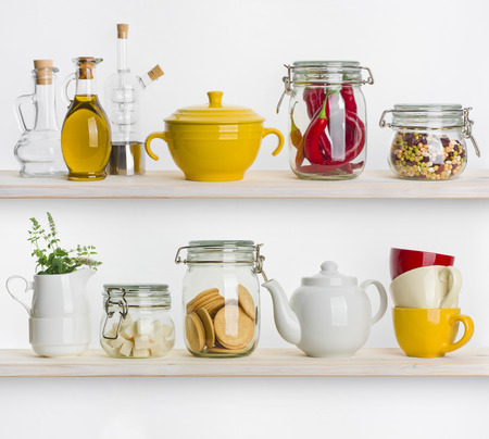 glass wall: Kitchen shelves with various food ingredients and utensils on white Stock Photo