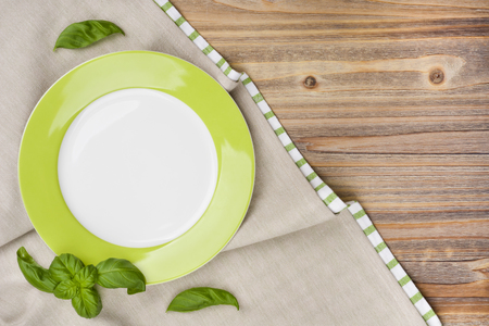 tablecloth: Plate with basil leaves on wooden table with tablecloth background Stock Photo