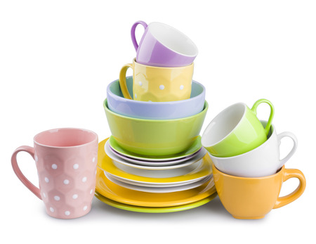 dishes: Stack of colorful plates and cups isolated on white background