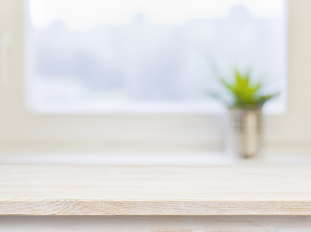 Wooden table on defocuced winter window background Imagens