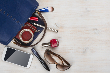 View on women bag stuff with copyspace on wooden background Stockfoto