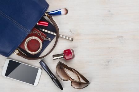 mujeres morenas: Ver en el bolso de las mujeres cosas con copyspace sobre fondo de madera