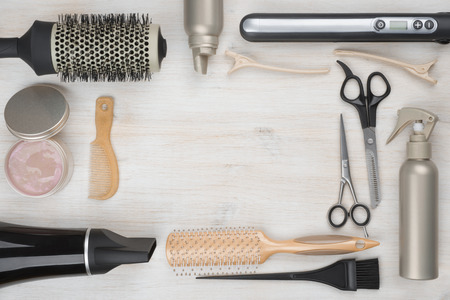 Hairdressing tools on wooden background with copyspace in the middle