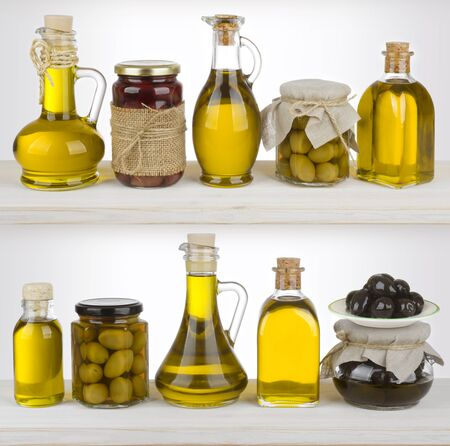 isolated on green: Olive oil bottles and jars standing on the shelf
