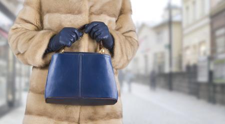 woman in fur coat: Woman in mink fur coat holding leather bag in hands