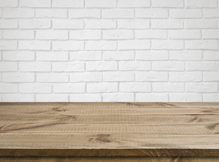 Rough wooden texture table over defocused white brick wall background Stockfoto
