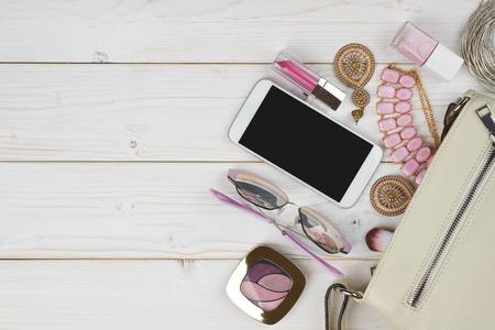 Vrouwelijke toebehoren die van handtas op houten achtergrond met copyspace vallen Stockfoto