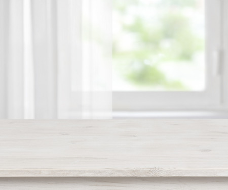 Wooden table surface on defocused half curtained window background Archivio Fotografico