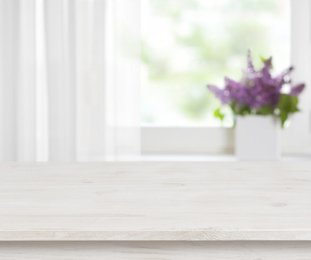 Drewniany stół na defocused okno z purpurowym doniczka tle