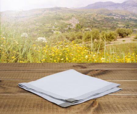 dishcloth: Folded linen napking on wooden table over mountain landscape background Stock Photo