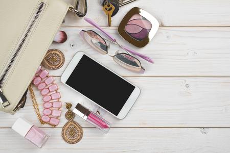 Vrouwelijk dingen vallen van handtas op houten achtergrond met copyspace