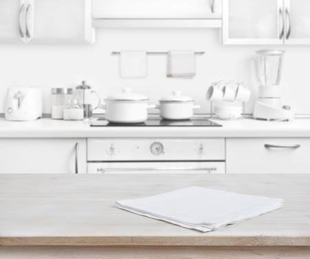 Houten tafel met een handdoek op vage witte moderne keuken achtergrond