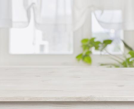Houten tafel over defocused groene bladeren en curtained venster achtergrond