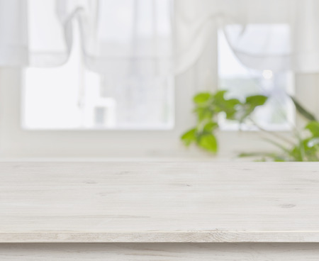 Wooden table over defocused green leaves and curtained window background