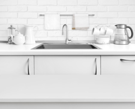White laminated table on blurred rustic kitchen sink interior background Standard-Bild