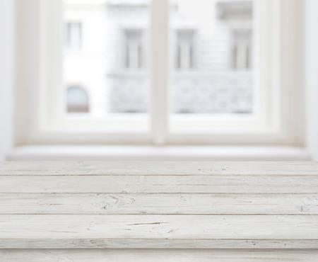 Leeg houten tafelblad voor productweergave over wazig raam