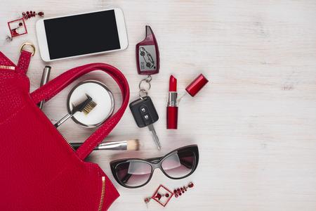 Vrouwelijke dingen en rode handtas op houten achtergrond met copyspace