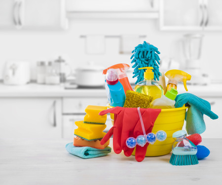 Various colorful cleaning products on table over blurred kitchen background Foto de archivo