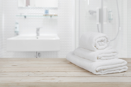 white towels: Blurred bathroom interior background and white spa towels on wood
